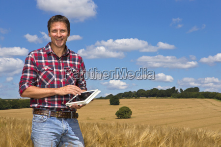 portrait smiling farmer with digital tablet
