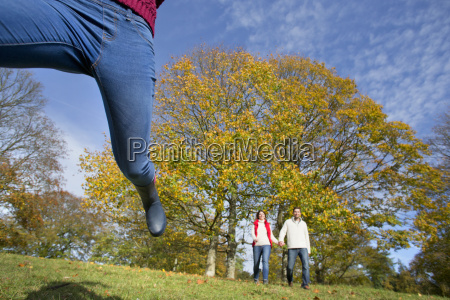 child leaping in autumnal forest with