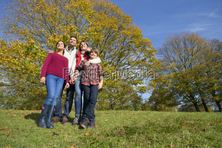 happy family standing together in autumnal