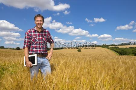 portrait smiling farmer with digital tablet