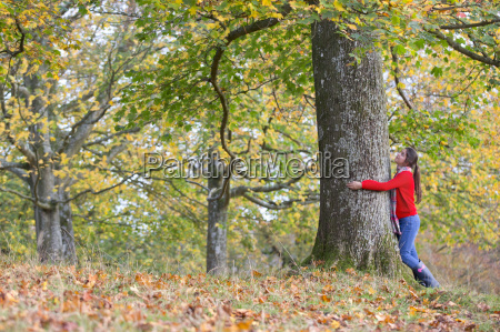 young girl hugging tree in autumnal