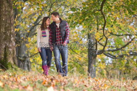 happy couple walking through autumnal forest
