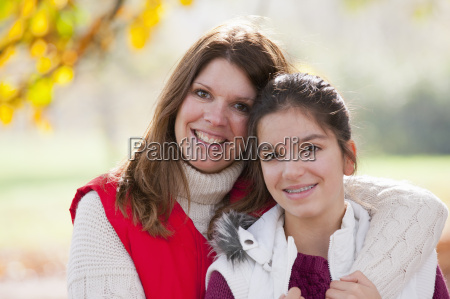 mother with arm around daughter looking