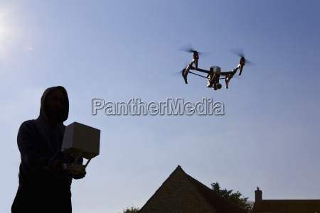 man operating surveillance drone in blue