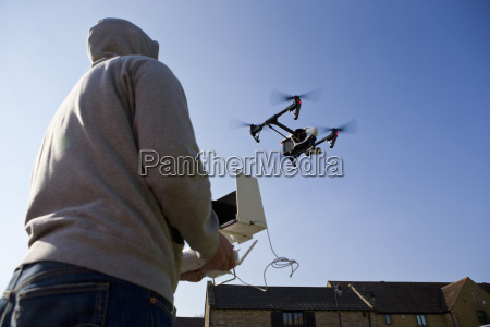 hooded man operating surveillance drone in