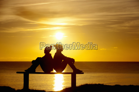 silhouette of couple sitting back to