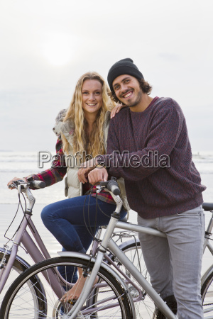 portrait smiling couple riding bicycles on