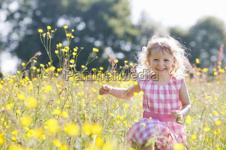 portrait of girl running through wildflower