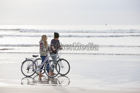 couple with bicycles looking at ocean