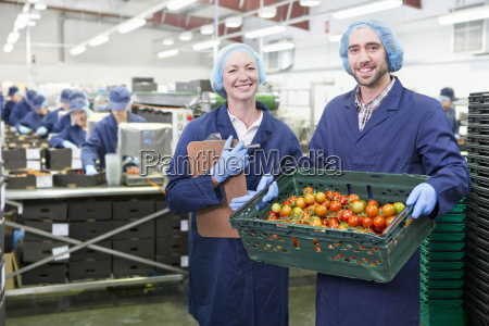 portrait confident workers holding crate of