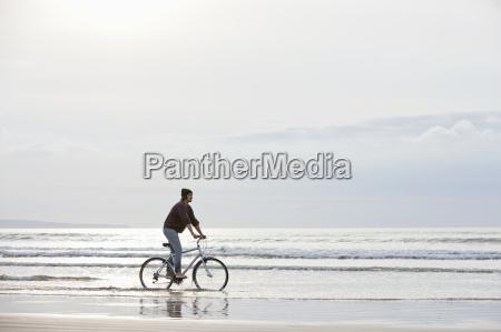 man riding bicycle in ocean surf
