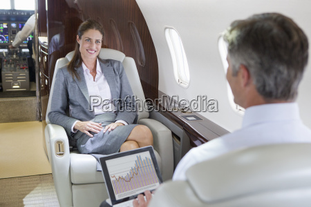 smiling businesswoman and businessman with digital