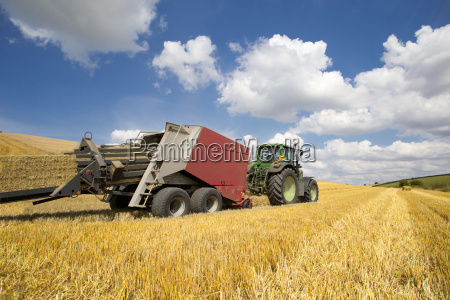 tractor baling straw in sunny rural