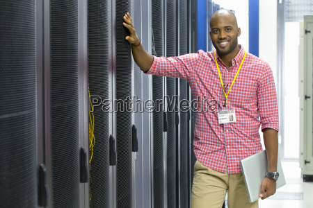 technician smiling at camera with laptop