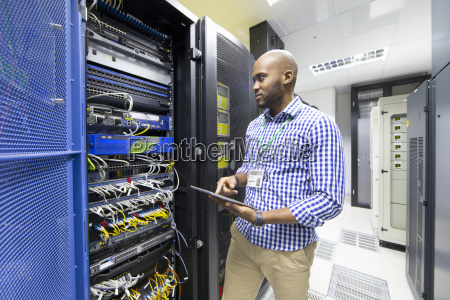technician with digital tablet checking server