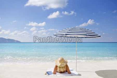 woman relaxing on sunny beach with