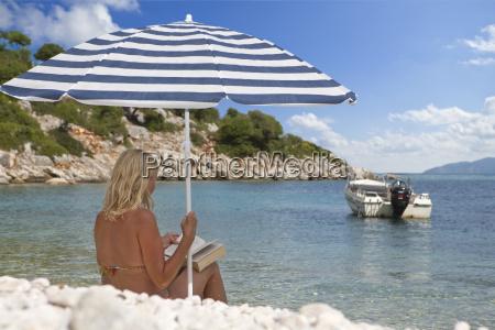 woman reading book under striped beach