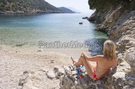 blonde woman in bikini sitting on