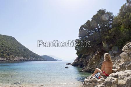 woman in bikini sitting on rocks