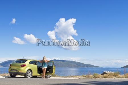 woman at car looking at sunny