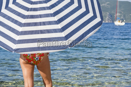 woman in bikini under striped beach