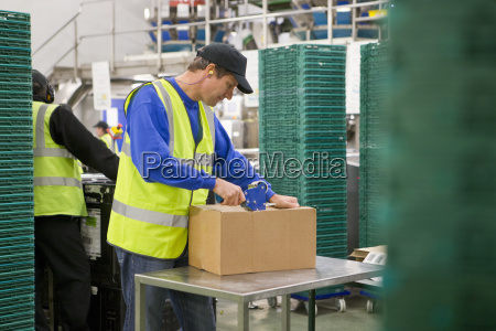 worker taping box in food processing