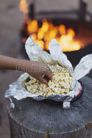 ein kleiner junge isst popcorn aus