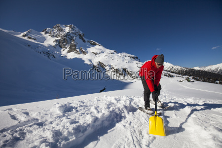 a climber shovels snow in order