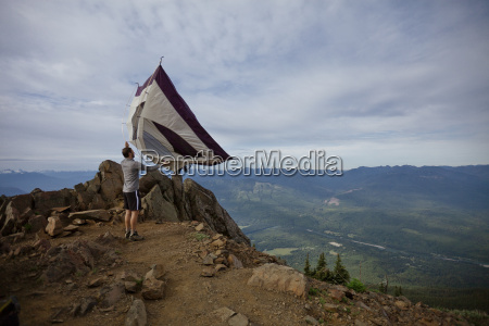 a hiker shakes his tent out