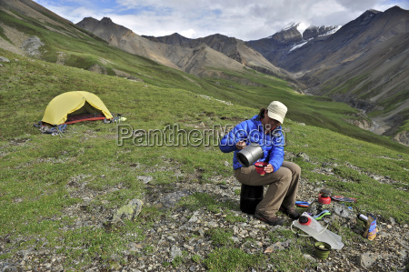 woman backpacker prepares meal at camp