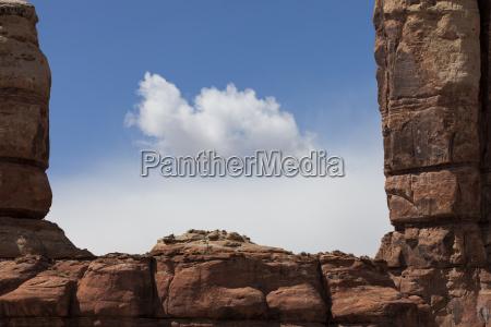 a cloud hovers in between rock