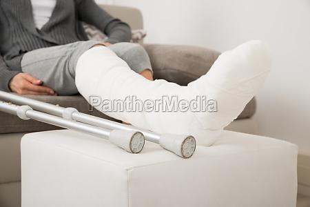 frau mit verputzten bein sitzt auf