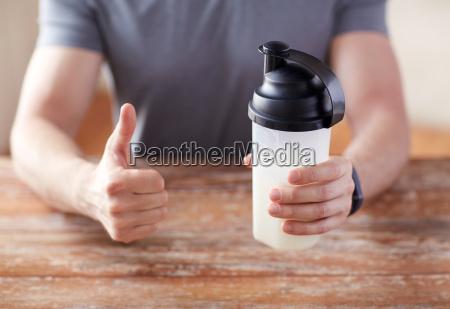 mann mit proteinschuettel flasche mit daumen