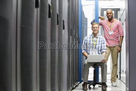 technicians with laptop looking at camera
