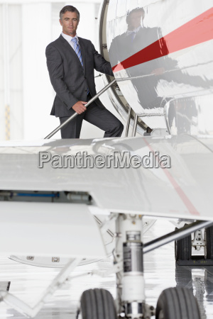 businessman boarding private jet and looking