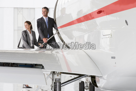 smiling businesswoman and businessman boarding private