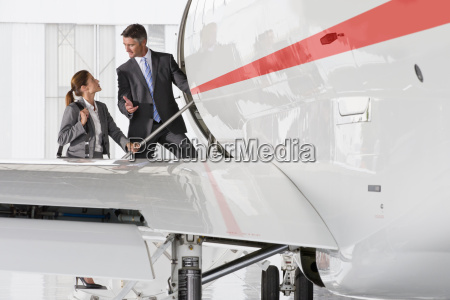 businesswoman and businessman boarding private jet