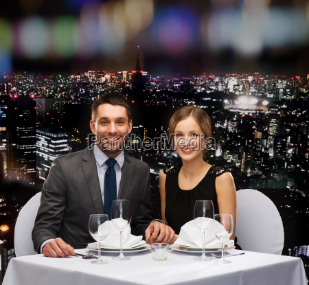 smiling couple holding hands at restaurant