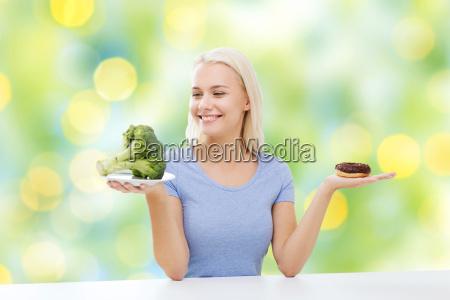 schmunzende frau mit brokkoli und donut