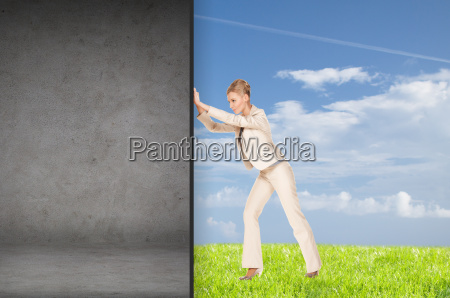 businesswoman pushing away concrete wall