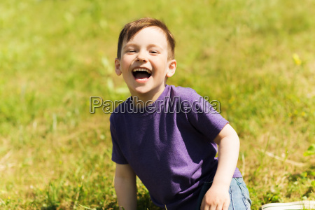 happy little boy sitting on grass