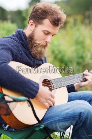 man with beard playing guitar in