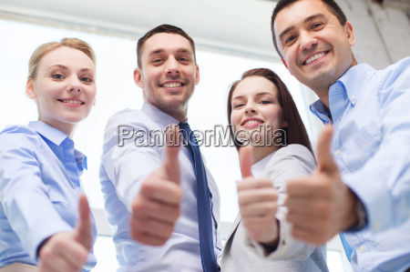 smiling business people showing thumbs up