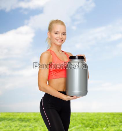 laechelnde sportliche frau mit glas protein