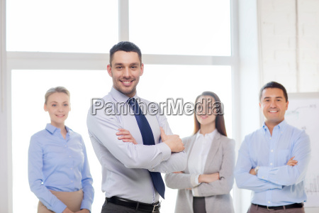 smiling businessman in office with team