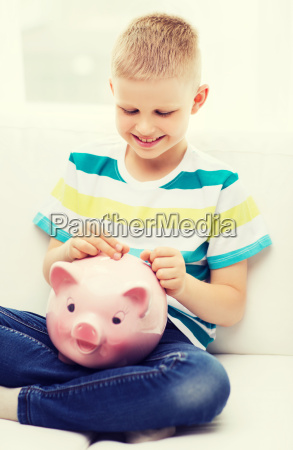 smiling little boy with piggy bank