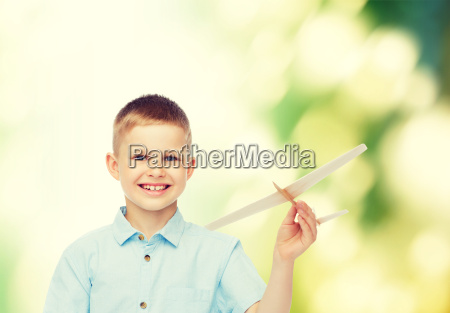 smiling little boy holding a wooden