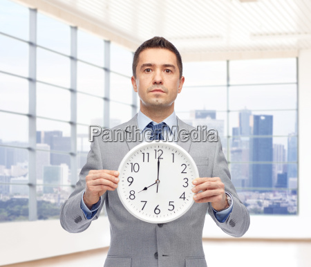 businessman in suit holding clock with
