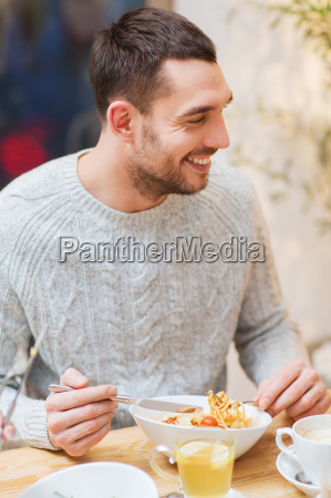 happy young man having dinner at