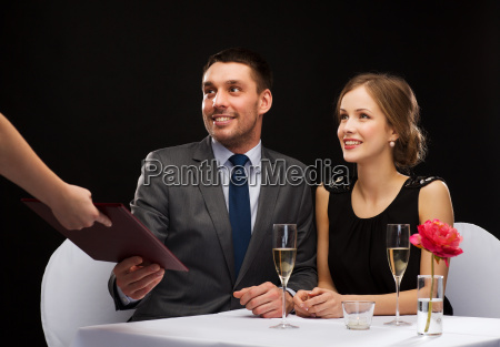 waiter giving menu to happy couple